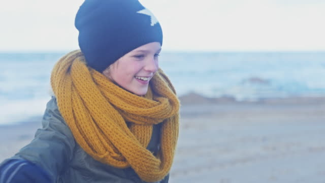 Beach in winter, young girl walking and laughing