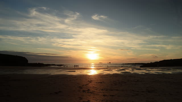 beach life in silhouette. treyarnon bay, cornwall sunset. - lying on back stock videos & royalty-free footage