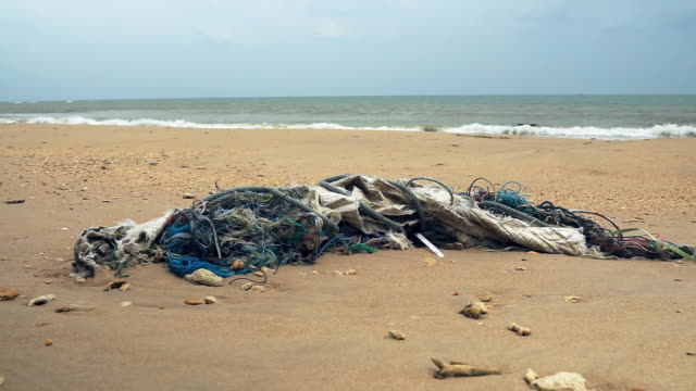 vídeos de stock e filmes b-roll de beach littered in fishing nets and plastic pollution washed up from the sea - sujo