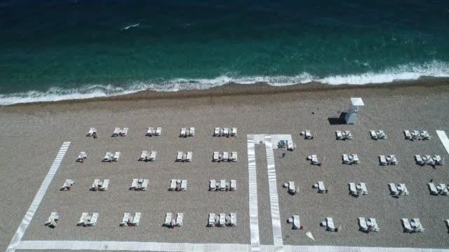 beach on the turkish mediterranean has set up social distancing areas and rules to guard against any new coronavirus outbreak. under a pilot program... - turkiet bildbanksvideor och videomaterial från bakom kulisserna