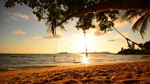 vidéos et rushes de plage sur l'île tropicale avec vide swing au coucher du soleil - hd format