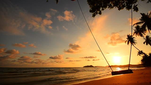 strand auf tropische insel mit leere schaukel bei sonnenuntergang - schaukel stock-videos und b-roll-filmmaterial