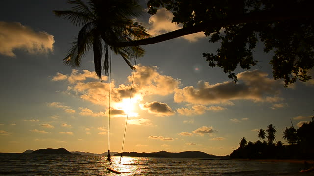 Beach on Tropical Island with Empty Swing at Sunset