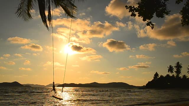 Spiaggia di isola tropicale con lo Swing al tramonto