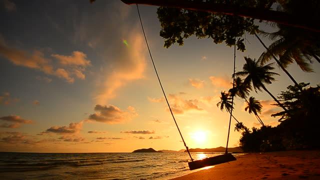 vídeos y material grabado en eventos de stock de playa de isla tropical con el swing en el crepúsculo - full hd format