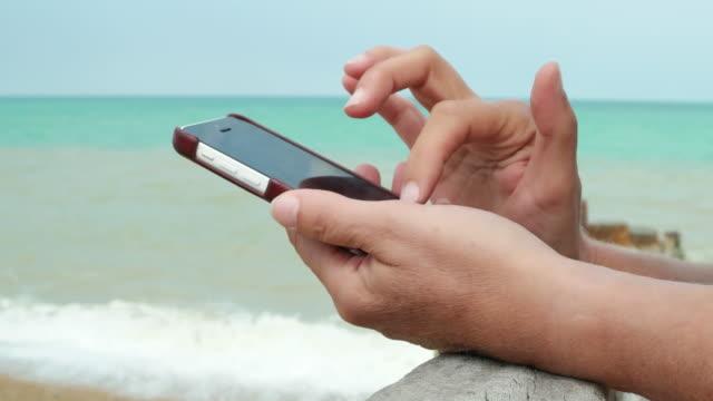 beach phone internet. woman's hand close. - sea robin bildbanksvideor och videomaterial från bakom kulisserna
