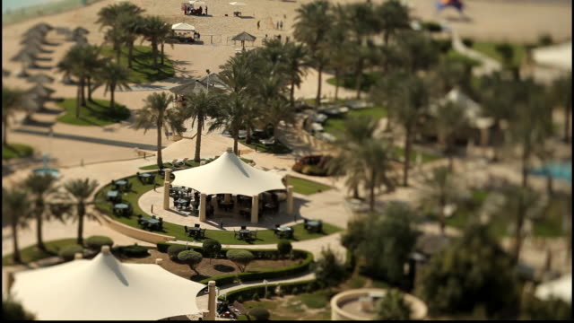 beach qatar highangle shot of a beach with palm trees sandy beach and white pagodas using a tiltshift lens giving a miniature or toy town effect - pagoda stock videos & royalty-free footage