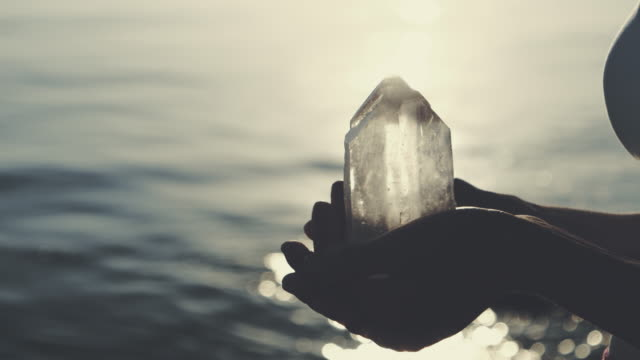 beach relaxation. holding healing crystals - buddhism stock videos & royalty-free footage