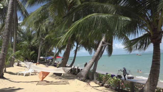 pan / a beach seller walk on sandy beach - gulf of thailand stock videos & royalty-free footage