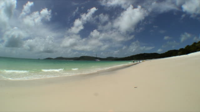 WS Beach shore with three people standing by inflatable raft in distance, Whitsunday Islands, Queensland, Australia
