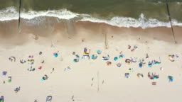 Beach showing colourful umbrellas and people relaxing on a summer day. Baltic Sea. Aerial view. Hel