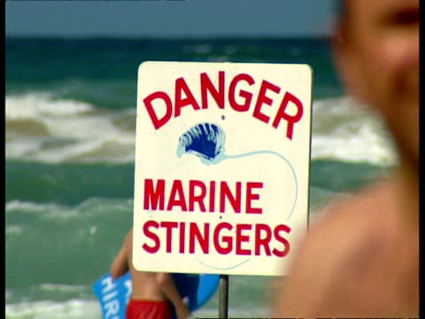 CU Beach sign Danger Marine Stingers, people walking through surf in background