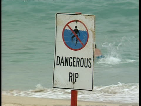 cu beach sign dangerous rip, man body boarding in background - 破れている点の映像素材/bロール