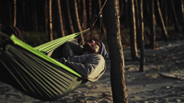 strand sonnenuntergang. spaß auf hängematte - hängematte stock-videos und b-roll-filmmaterial
