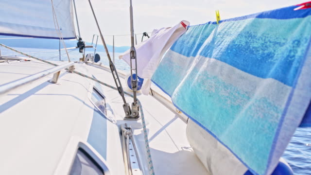 vídeos de stock e filmes b-roll de 4k beach towels blowing in the wind, drying on sunny sailboat, real time - toalha