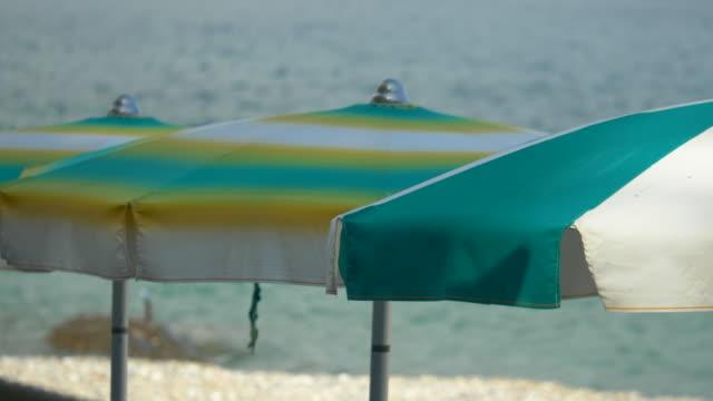 stockvideo's en b-roll-footage met beach umbrellas in a luxury resort town in italy, europe. - slow motion - zonnescherm gefabriceerd object
