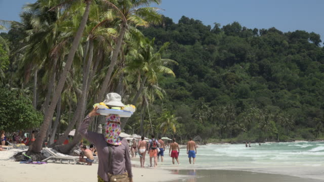 Beach vendor and tourists walking at Sao Beach