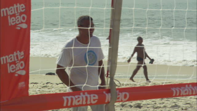 a beach volleyball player crouches at the net in anticipation of the ball. - volleyball net stock videos & royalty-free footage