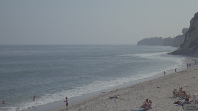 h-d beach w/activity (paradise cove); pan to pier - southern california stock videos & royalty-free footage