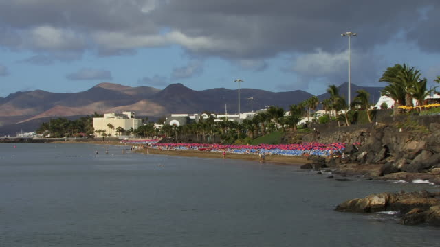 ws, beach with mountains in background, puerto del carmen, lanzarote, canary islands, spain - unknown gender stock videos & royalty-free footage