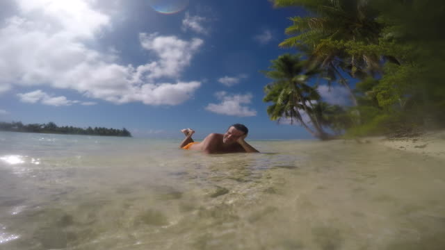 beach with pebbles (coral) with coconut trees, man lying in the sea - tahitian culture stock videos & royalty-free footage