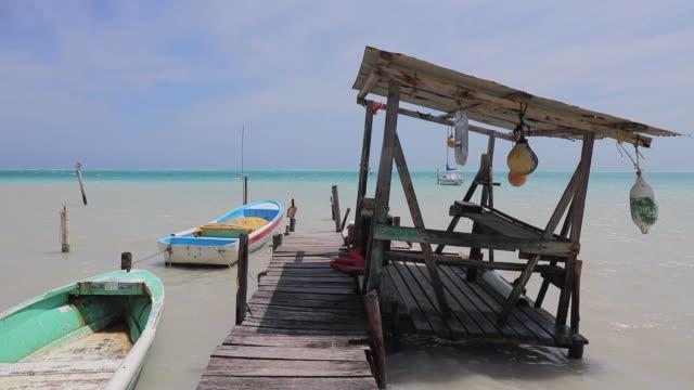 strand mit pier shack und boote auf karibik-insel - belize / caye caulker - cay insel stock-videos und b-roll-filmmaterial