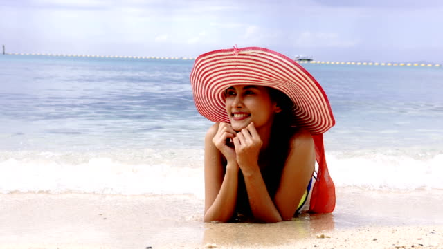 beach woman sun tanning on summer tropical vacation. - cappello video stock e b–roll