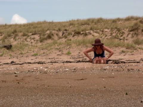 vídeos de stock, filmes e b-roll de praia de ioga: de estar estende-se para frente - boa postura