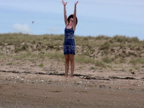 vídeos de stock, filmes e b-roll de praia de ioga: alongamento e namaste - boa postura