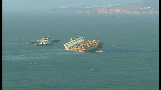 fears of oil and chemical spillage on devon coast wide shot of msc napoli in sea cliffs and coastline - itv weekend evening news stock-videos und b-roll-filmmaterial