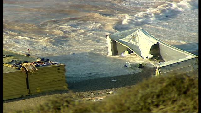 fears of oil and chemical spillage on devon coast large shipping containers washed up on beach police officers on road next to beach - itv weekend evening news stock-videos und b-roll-filmmaterial