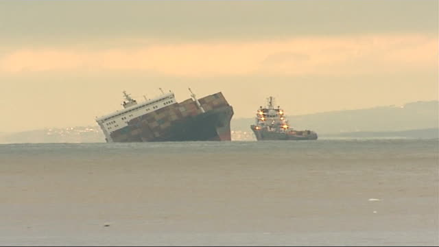 locals seize washed-up goods; long shot of listing msc napoli at sea - gestrandet stock-videos und b-roll-filmmaterial