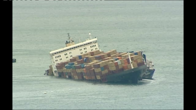 beached msc napoli cargo ship: operation to remove containers; long shot napoli with bigfoot crane beside msc napoli listing in water - bigfoot video stock e b–roll