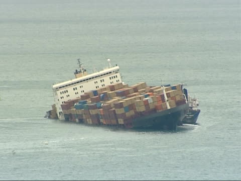 operation to remove containers views of listing ship and crane barges ENGLAND Devon Branscombe Bay EXT Long shots listing cargo ship MSC Napoli off...