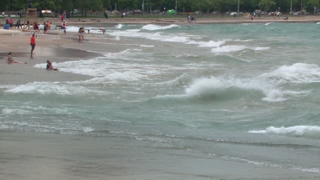 beach-goers at a chicago beach stay close to shore during a swim ban as the national weather service had issued a beach hazards statement on july 24... - 破れている点の映像素材/bロール
