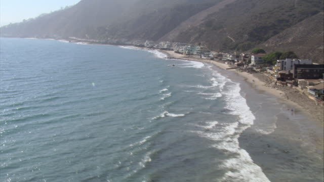 AERIAL Beach-goers enjoying the beach and houses at base of mountain along Pacific Coast Highway / Malibu, California, United States