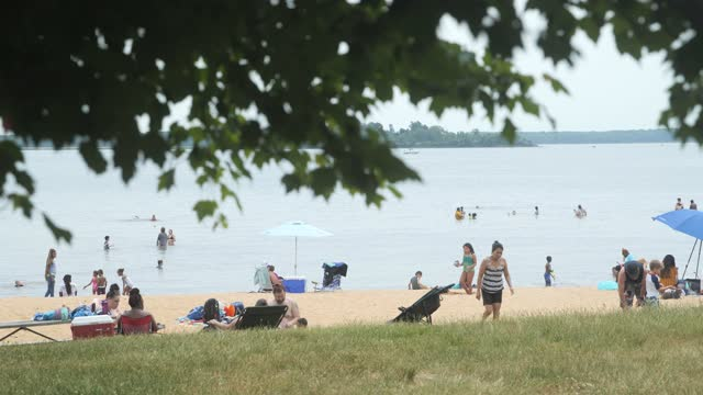 beachgoers play and relax at the beach at gunpowder state falls on may 22, 2021 in middle river maryland. nearly 6 000 covid-19 vaccine shots have... - maryland us state stock videos & royalty-free footage