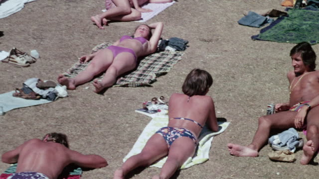 ha beachgoers sunning / united kingdom - sunbathing stock videos & royalty-free footage