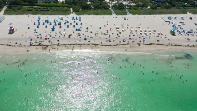 beachgoers take advantage of the opening of south beach on june 10 2020 in miami beach florida miamidade county and the city of miami opened their... - miami dade county stock videos & royalty-free footage