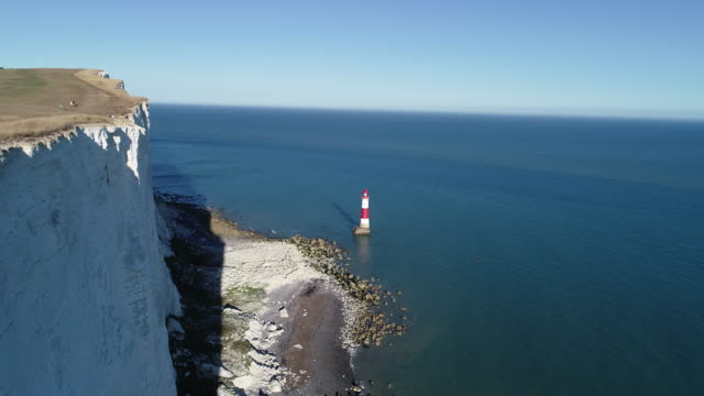 beachy head lighthouse aerial view moving forward over white cliffs - english channel stock videos & royalty-free footage