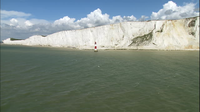 Beachy Head Lighthouse stands in the water near the White Cliffs of Dover in East Sussex, England.