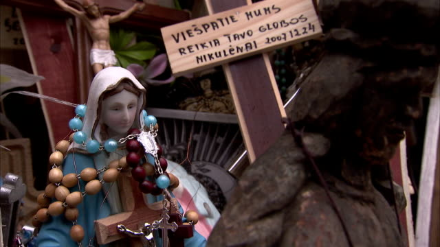 Beads wrap around a religious statue at the Hill of Crosses. Available in HD.