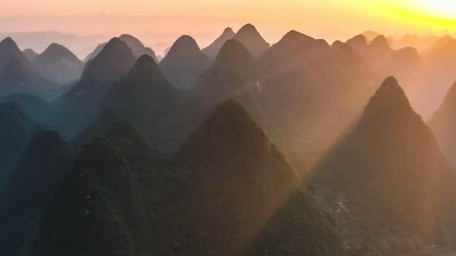 strahlen des sonnenlichts durch den karstgipfelhaufen in yangshuo, der einen unglaublichen dingdar-effekt bildet - gebirgskamm stock-videos und b-roll-filmmaterial