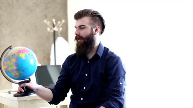 Beard hipster businessman pointing to globe