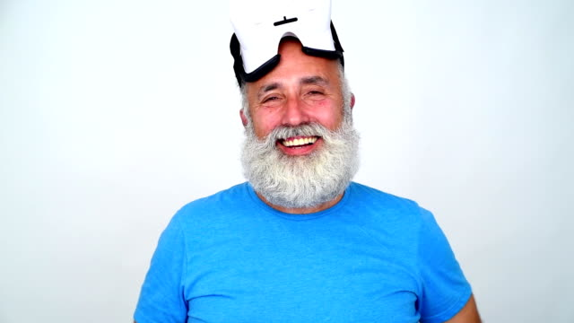 Beard old man takes off his glasses virtual reality and happily smiling on a gray background