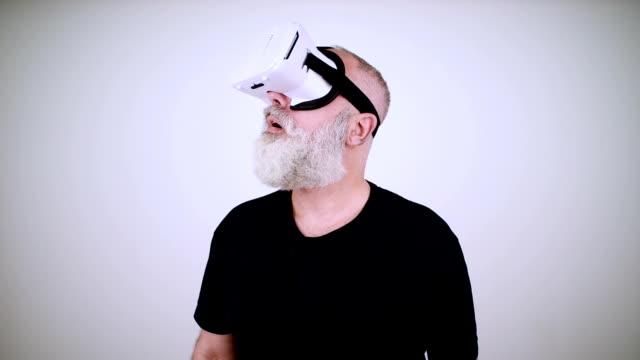 Beard senior man looking up using virtual reality glasses on black background