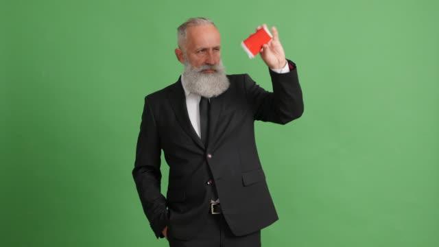 Bearded adult businessman drinks coffee on green screen