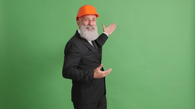 ひげを生やした大人のビジネスマンは緑の背景に何かを提示します。 - 50 59 years点の映像素材/bロール