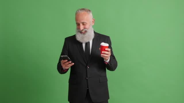 vídeos de stock, filmes e b-roll de empresário de adulto barbudo está usando um smartphone sobre um fundo verde - 50 59 years