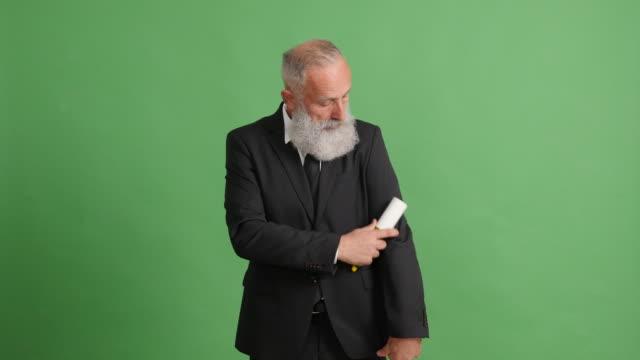 bärtige erwachsenen geschäftsmann führt einen anzug in der reihenfolge auf einem grünen bildschirm - 50 59 years stock-videos und b-roll-filmmaterial